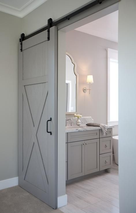gray walls highlight a gray barn door on black rails leading to an en suit bathroom featuring a. Black Bedroom Furniture Sets. Home Design Ideas
