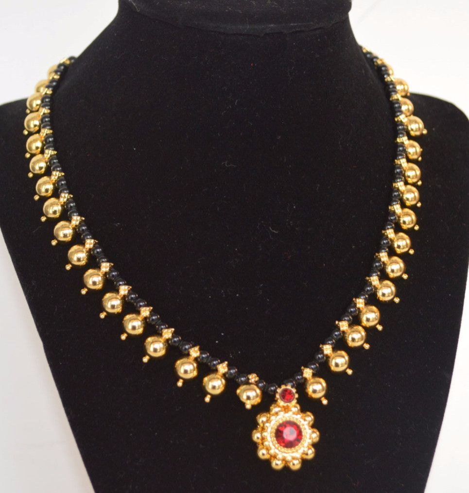 Kopm long mangalsutra with black beads and round pendant