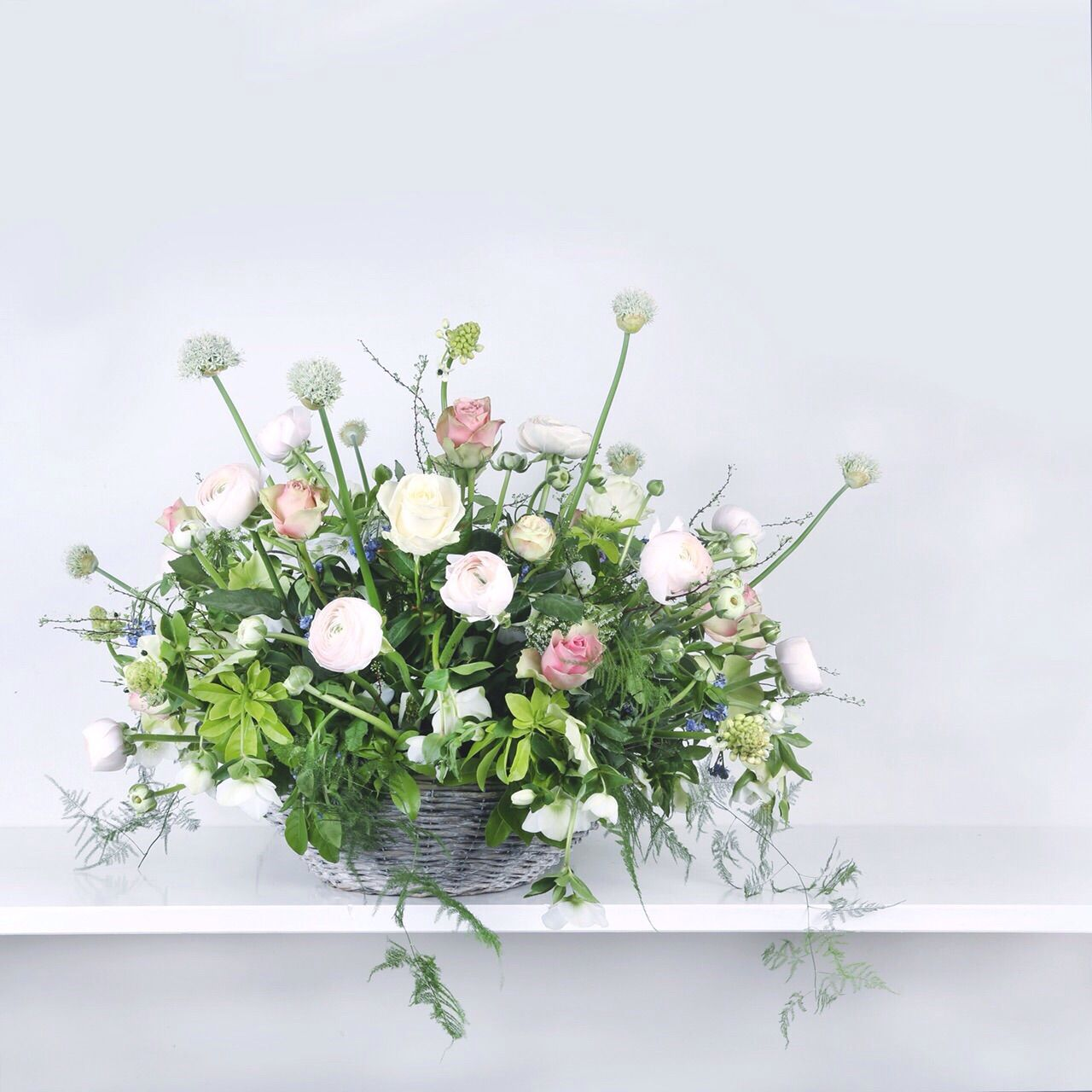 funeral arrangement in basket with pastel colors