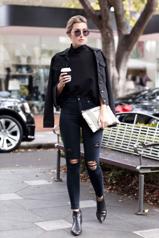 Black denim jacket, black oversized mock neck shirt, black skinny distressed jeans, black leather pointed toe ankle boots