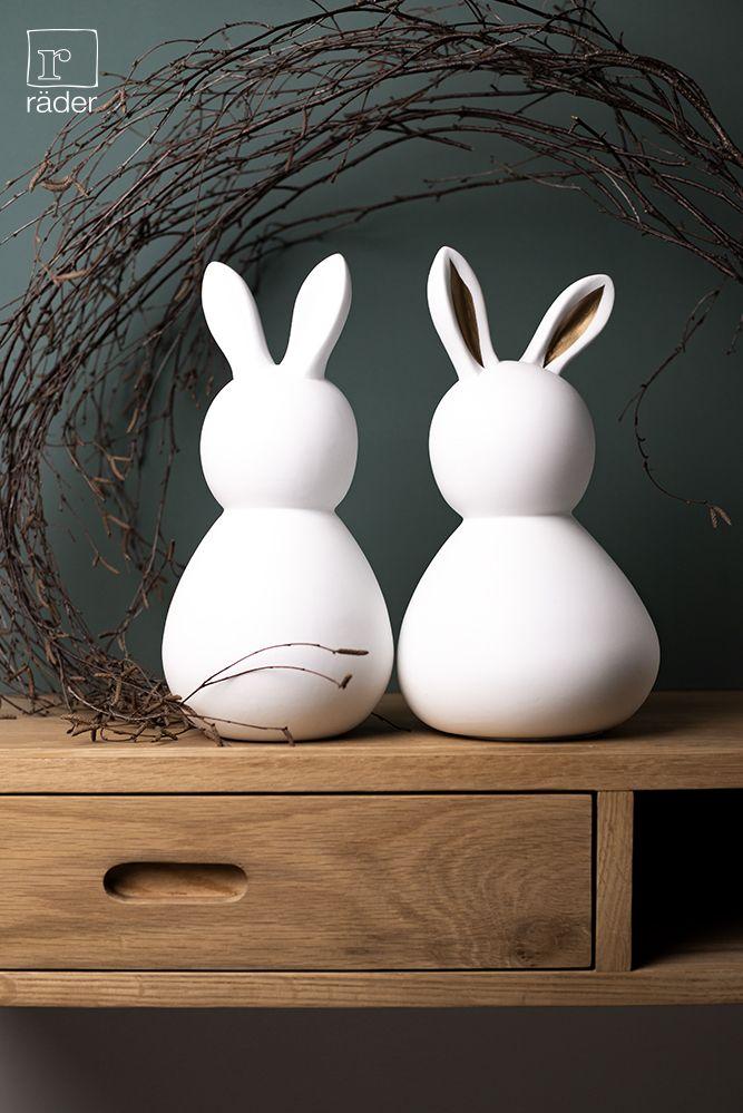 Große Porzellanhasen für das Osterfest: Das Osterhasenpaar hat es sich auf einem Regal gemütlich gemacht. Der schlicht weiße Herr und die Dame mit goldenen Hasenohren geben ein schönes Paar ab. Das unglasierte Porzellan lässt die Hasen schneeweiß aussehen. Design: Frütel. #frohe #ostern #happy #easter #decoration #dekoration #osterdeko #interiordesign #osterhase #osterhasen #bunny #bunnies #schneeweiß #porzellan #weiß