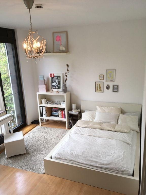 Lichtdurchflutetes Schlafzimmer mit weißem Holzbett und Dielenboden ...