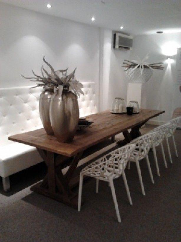 mooi tafel met witte stoelen en bank  grote potten op de