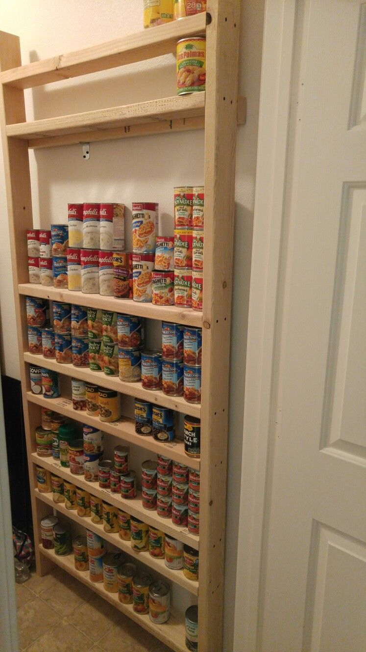 "Our canned storage. I used a bunch of 2x4 scraps and two new 2x4's, assembled with 3.5"" self tapping screws. Shelves are 34"" wide, which fits 10 cans of Progresso soup with a slight gap. I made it 7' tall so it would make good use of the upper dead space on the wall. I also used a single sheet metal L bracket to mount the shelves to a wall stud."