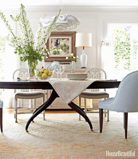 Vintage-inspired furniture and a contemporary chandelier create a cool, modern contrast in the formal dining room.