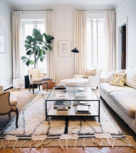 layered rugs on a parquet floor, french doors framed by curtains, large plant in front of one door.