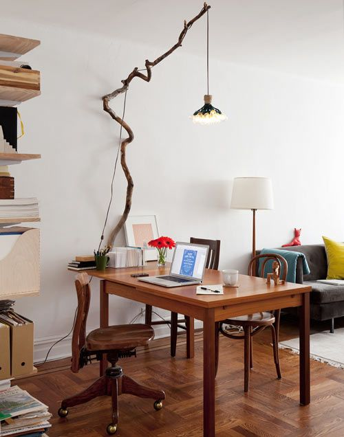 """Kimi Weart and Paul Galloway:    This is our workspace/dining table for parties. The chairs are all street finds from over the years. I made the hanging light, and Paul indulged me when I said, """"I want to nail a big branch into the wall.""""    ViaDesign Sponge."""