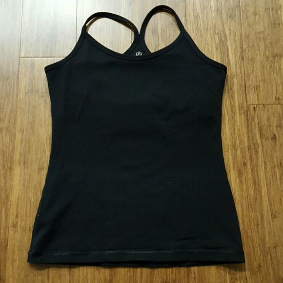 Lululemon black tank Fair to used condition black tank with built-in unpadded shelf bra. No holes to put pads in. Tank has some general wear by look and feel but is still functional and wearable. Two logos, one inside with more wear, one outside in better condition. No rip tag or size dot, likely an older model. I wear lululemon size 6 tops and this fits me. Measures approx 14.5 inches armpit to armpit. Priced accordingly. Just washed and line dried. No trades or PayPal. Cheaper on Merc…