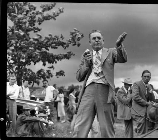 """Unidentified preacher speaking at """"Singing on the Mountain"""" gospel festival, with onlookers in background, Grandfather Mountain, Linville,  North Carolina, 1940's."""