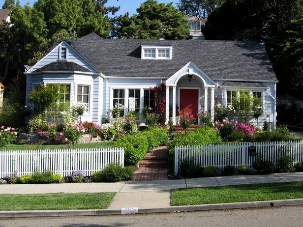 a light blue house with arched front door at the end of a brick walkway also boasts a front yard cottage style landscaped garden complete with various - Front Yard Cottage Garden Ideas
