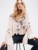 Siren Song Top   Embroidered with a beautiful and colorful floral design this flowy top features a V-neckline with adjustable tie detailing.  Boho wide sleeves with flared ruffle cuffs and an elastic waistband.