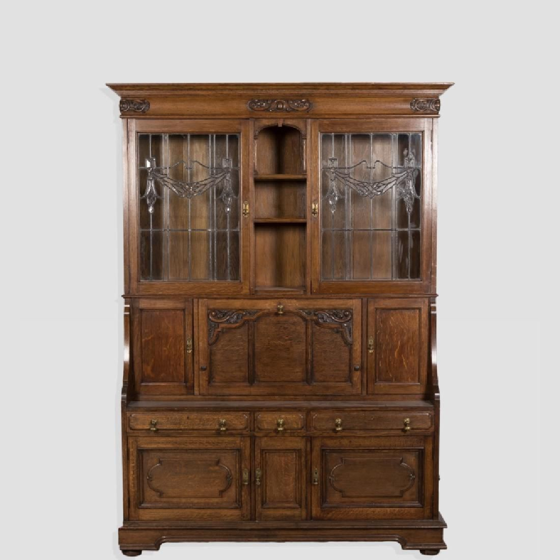 Large carved oak breakfront with leaded glass doors and drop down secretary desk
