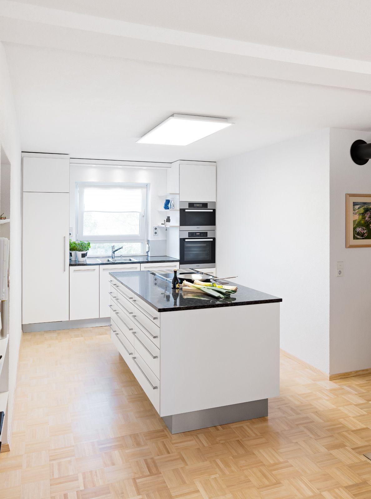 Moderne Weisse Kuche Mit Edelstahlgriffen Kochinsel Mit Dunkler Arbeitsplatte Und Dunstabzug Nach Unten