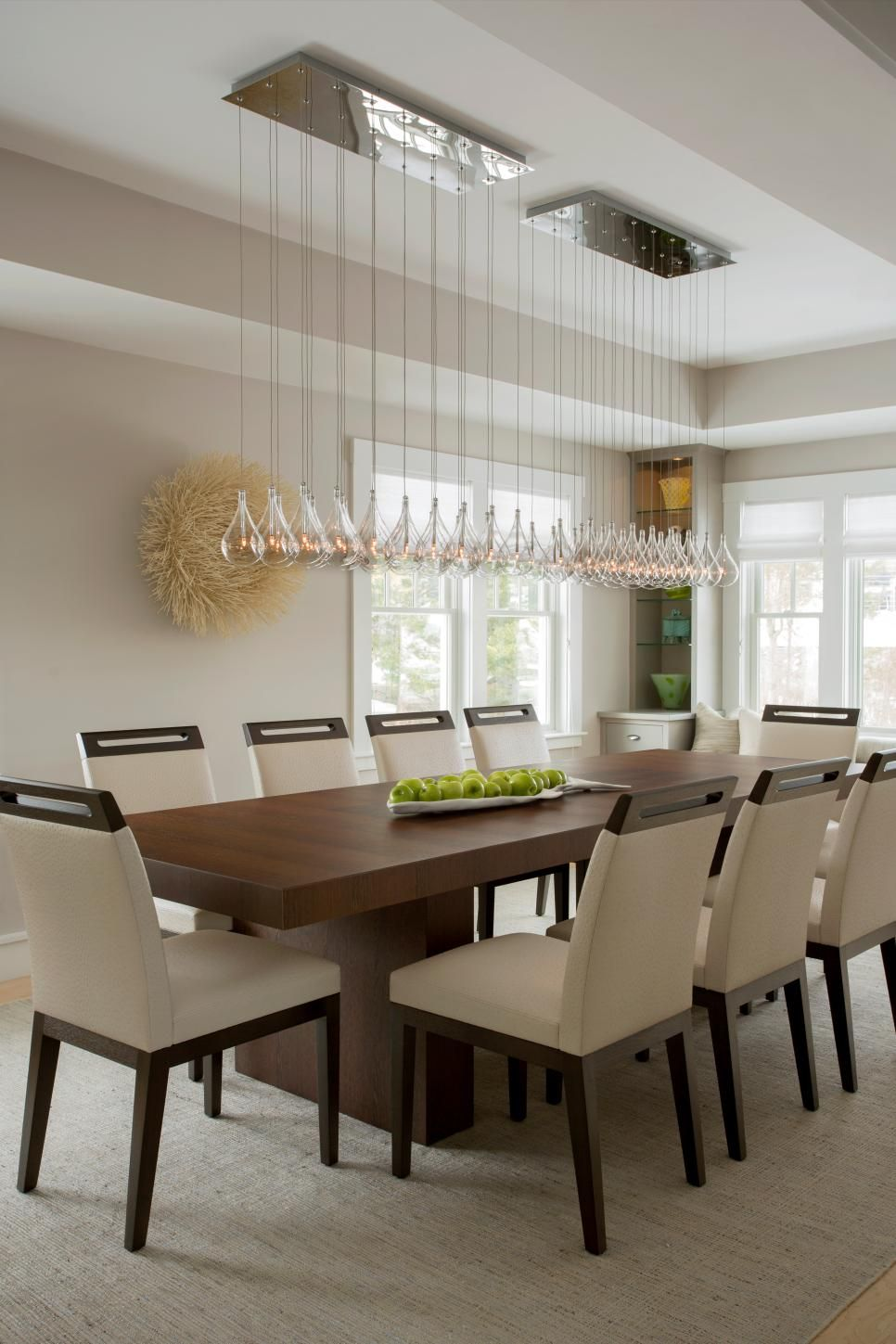 This Modern Dining Room E Features A Long Gl Chandelier Hung Over Warm Wood Table Adding Touch Of Elegance To The Stark