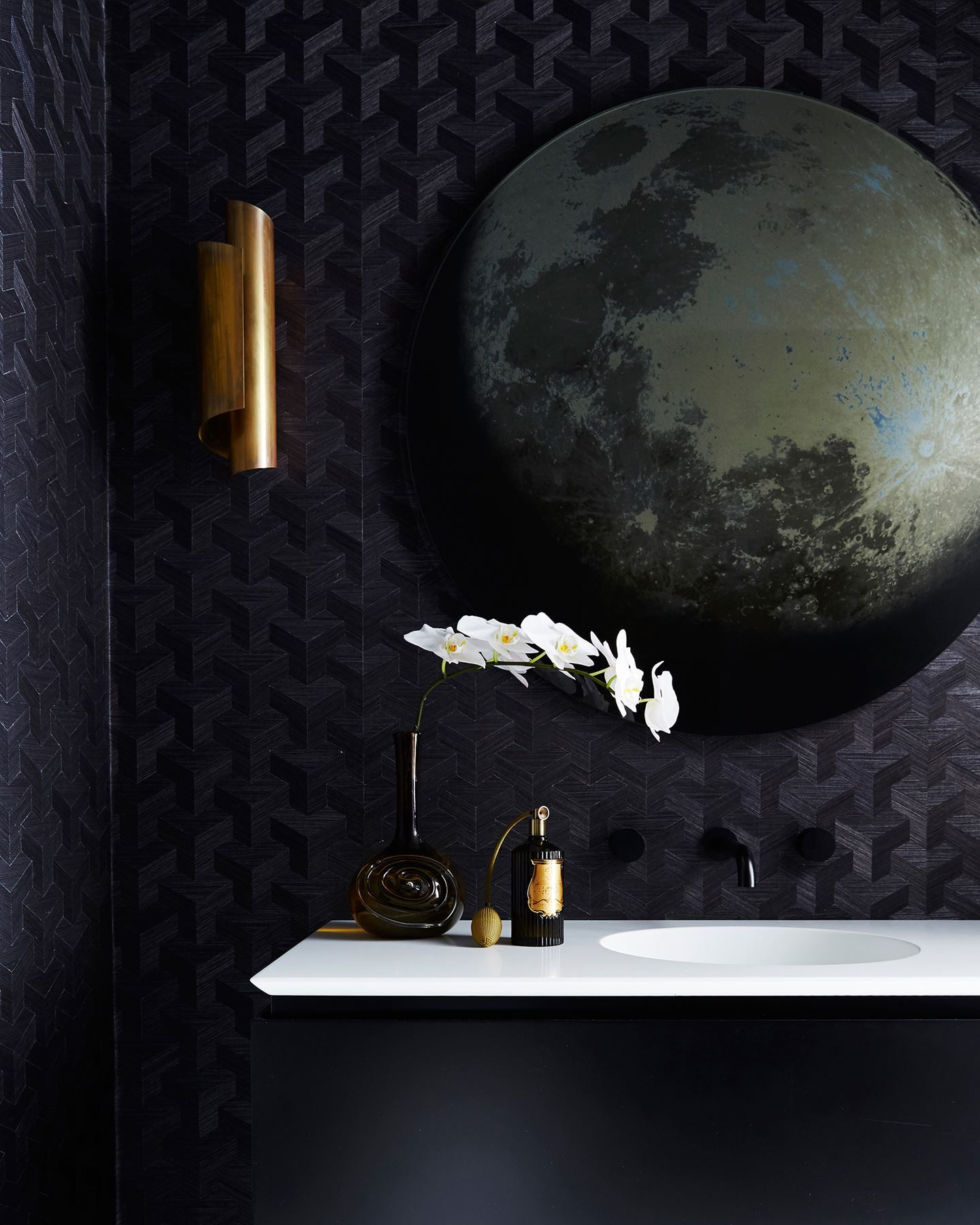 """Visitors are always wowed by the edgy powder room. """"The black wallpaper, black tapware and black ceiling give the powder room a moody ambience, and there's the concealed door that opens up to the hidden laundry,"""" says Poppy. """"It adds an element of the unexpected, so we call it the Bat Cave!"""" The brass wall lamp, bought online at 1stdibs.com, once adorned the walls of a luxury hotel in Switzerland. Corian benchtop with integrated basin. Xanadu sisal wallcovering, Unique Fabrics."""