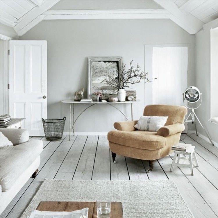 Un salon campagne chic blanc du parquet au plafond réveillé par un gros fauteuil orange