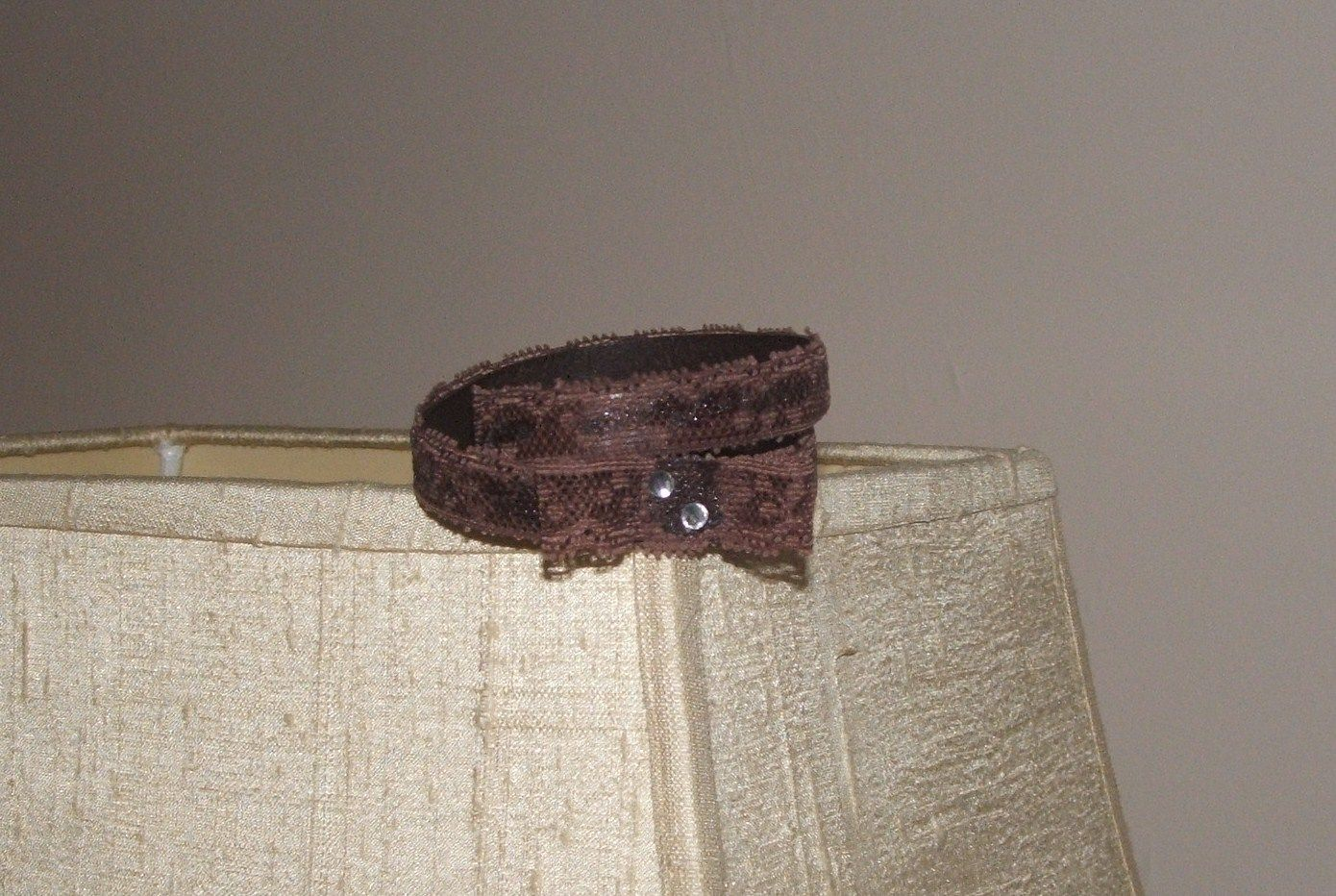 Pulseira em cabedal plano castanho escuro de duas voltas com aplicação de renda e laço em renda   Ref. 2404113 - 12€