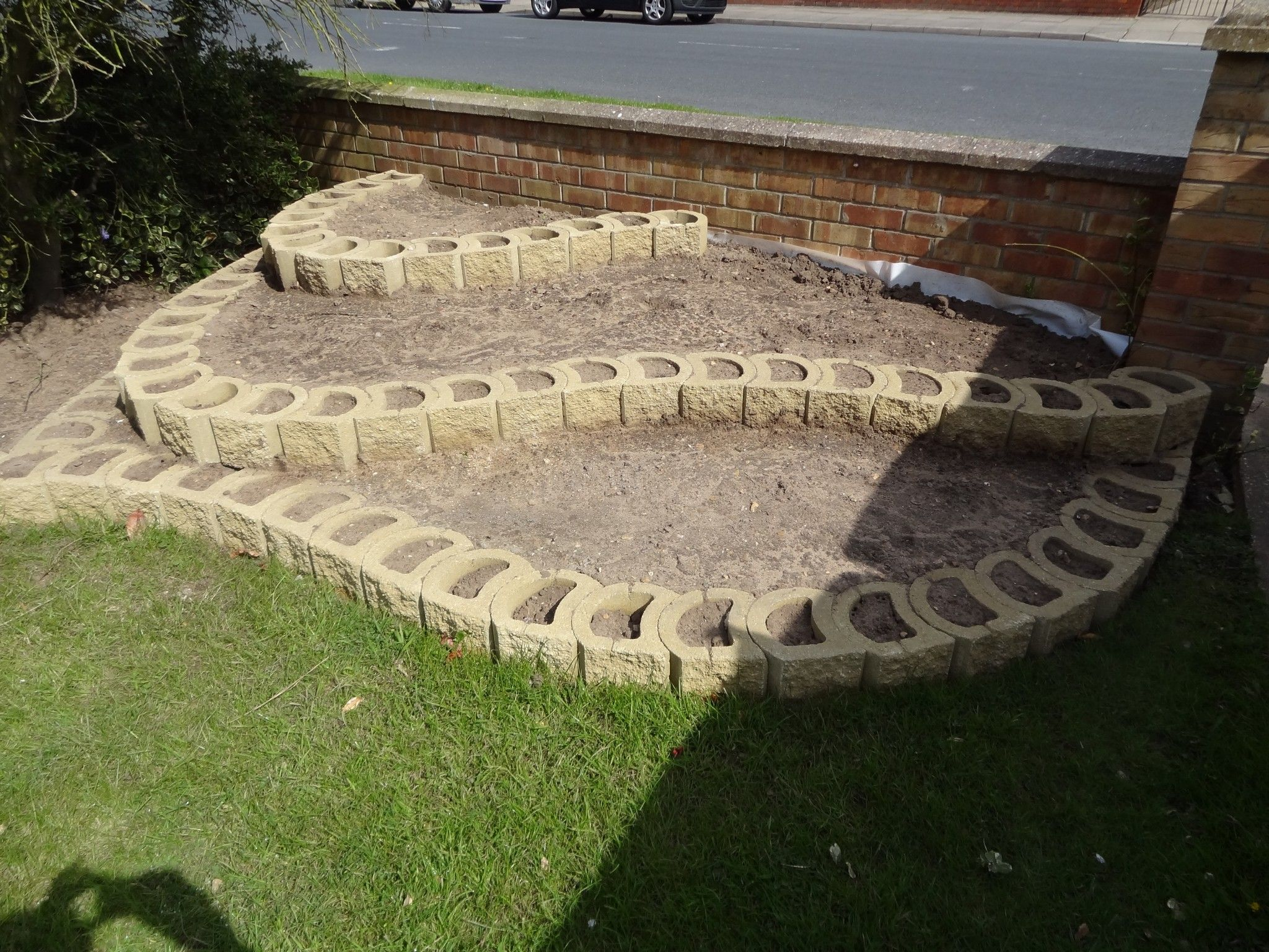 Terraforce Hollow Core Retaining Wall Blocks Being Used To Create A Low Terraced Flower Bed Retaining Wall Blocks Garden Wall Retaining Wall