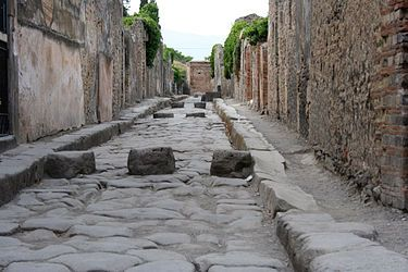 *POMPEII, ITALY:    A paved street, the blocks in the road allowed pedestrians to cross the street without having to step onto the road itself which doubled up as Pompeii's drainage + sewage disposal system. The spaces between the block allowed horse drawn carts to pass along the road.
