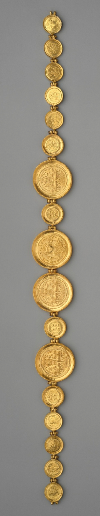 Girdle with Coins and Medallions, circa ca. 583, reassembled after discovery; Byzantine. This incomplete, massive gold girdle composed of a series of solidi & medallions may have been worn as an insignia of office. The four medallions depicting the emperor Maurice Tiberius for him in 583. Coins are stamped CONOB, indicating that they were minted in the capital city. There is also a coin of Theodosius II (r. 402–50) & four from the brief joint rule of Justin I and Justinian in 527.