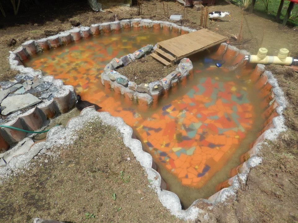 Dise o de estanque con piso en mosaico una isla en el for Como construir un estanque en el jardin
