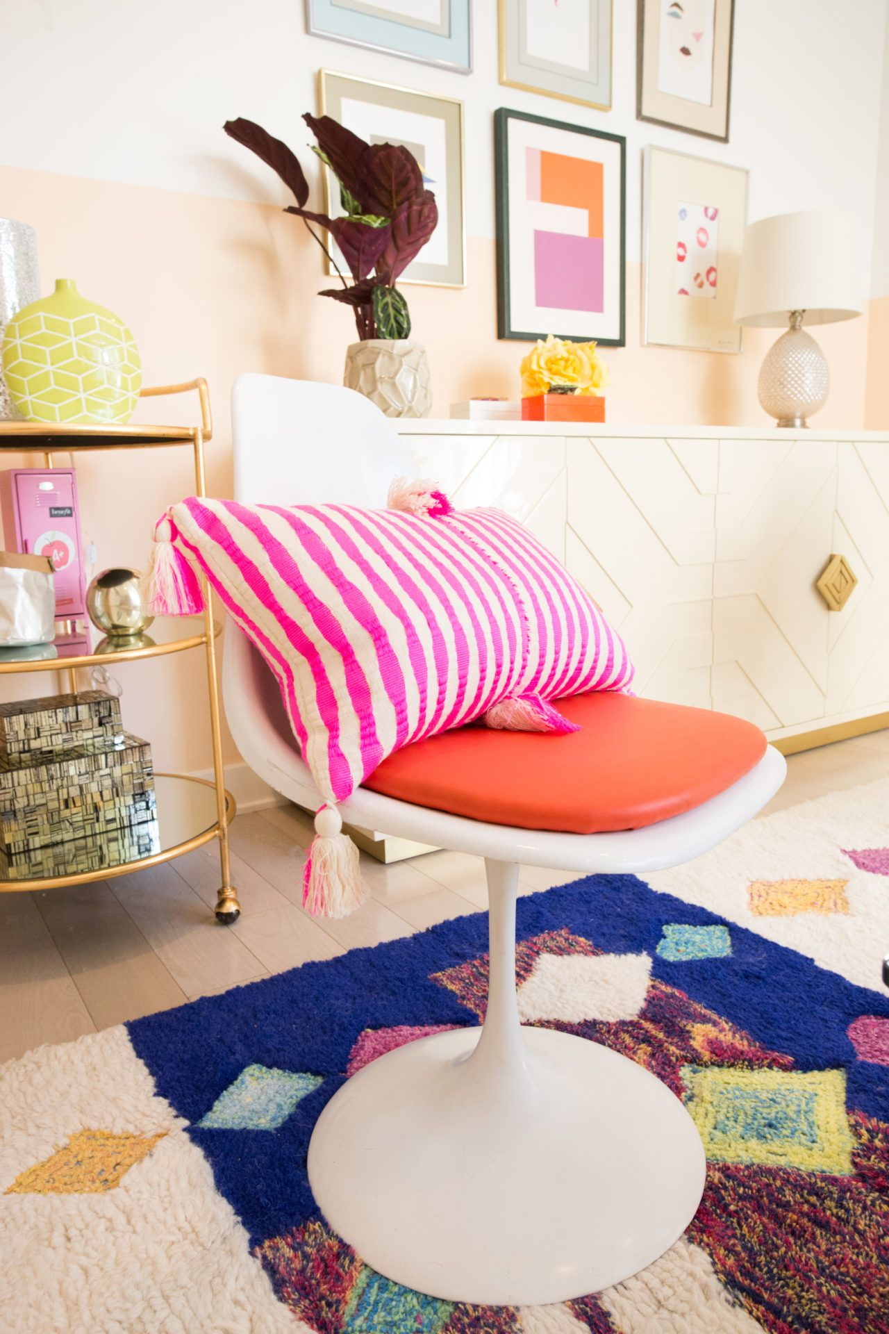 This vintage tulip chair, paired with a bright pink striped pillow is a pop of colorful fun for a lively living room design!