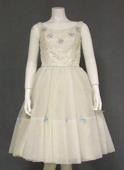"""$165  A charming 1960's dress in ivory nylon chiffon. Fitted sleeveless bodice with shimmering iridescent sequin trim and blue sequined flowers. Ivory and blue chiffon cord waistband. Dress has a full skirt with dainty blue chiffon bows all the way around (dress has an attached crinoline, but is shown here with an additional small crinoline... not included). Dress is fully lined. Rear metal zipper.   Size:  33"""" bust, 23"""" waist, full hips. Approximately 38 1/2"""" from shoulder to hem."""