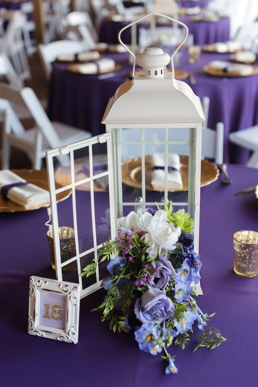White Lanterns And Floral Centerpieces On Purple Linens Wedding Reception Table Decor