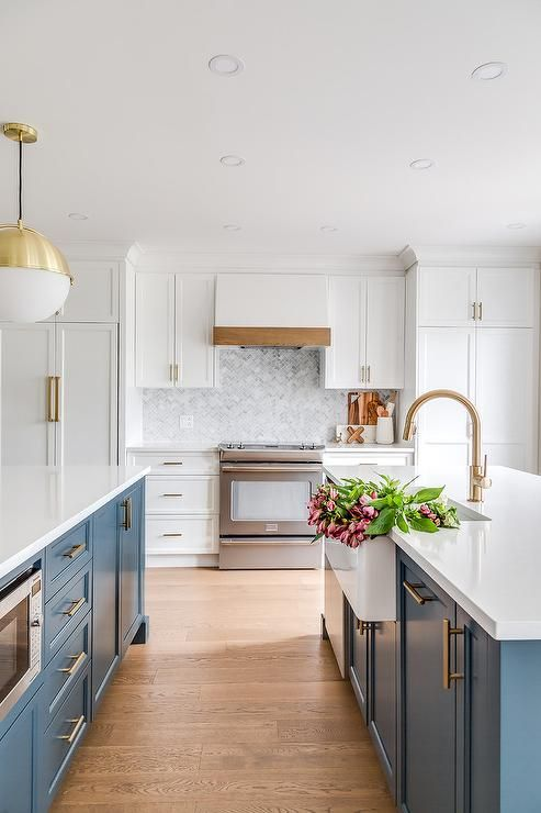 Beautiful blue and white kitchen features two blue islands accented ...