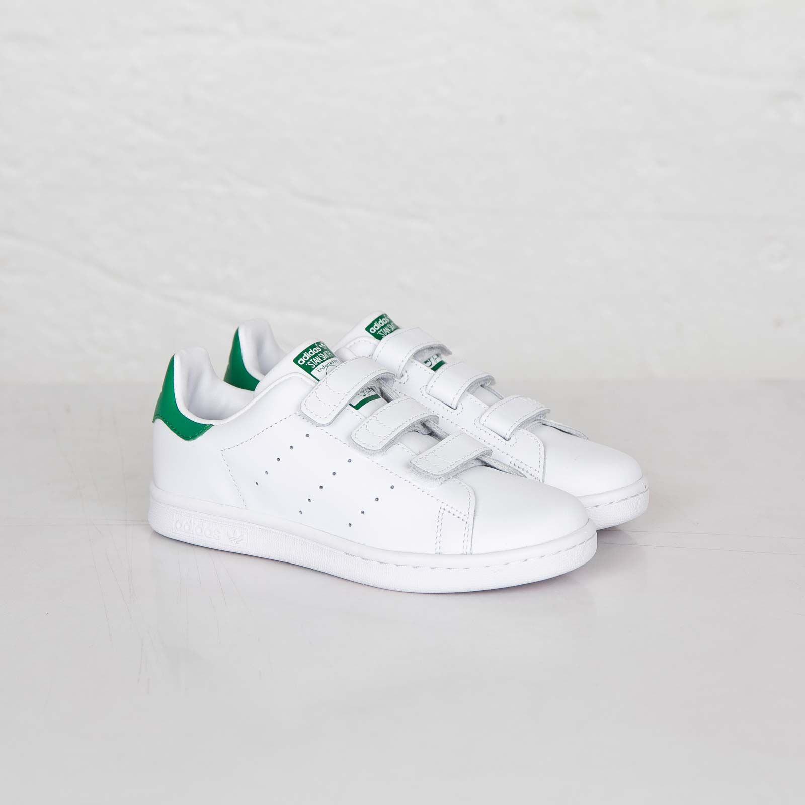 men's adidas stan smith with suitcase getting into taxi