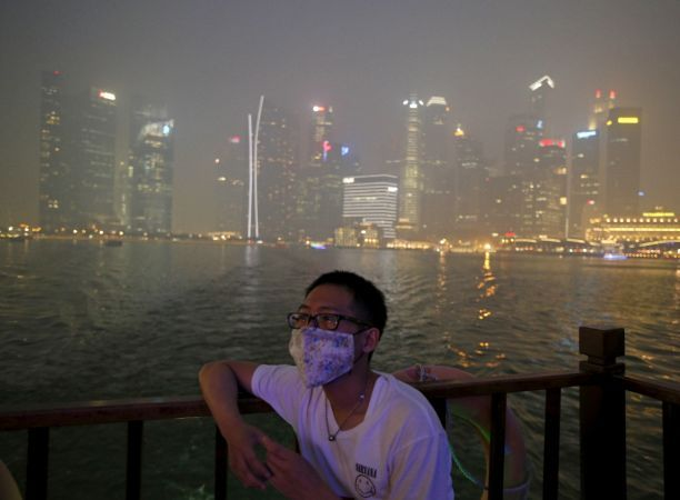 A man wearing a mask watches from a boat as he passes the haze-shrouded central business district in Singapore September 24, 2015.
