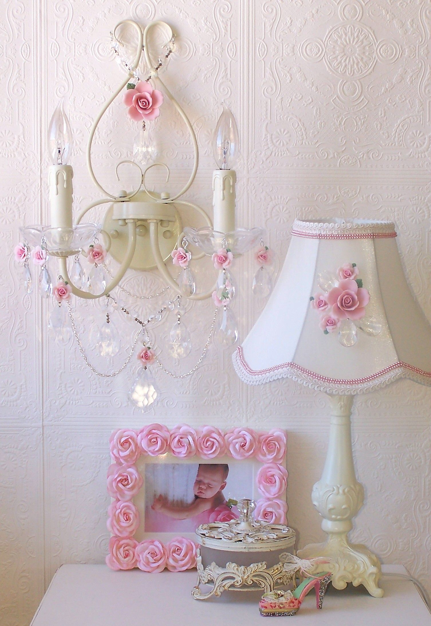 Create soft mood lighting with this Romantic double-light Wall Sconce in antique white. It has been adorned with the most delicate pale pink porcelain roses in full bloom and decorated with sparkly crystal chains, a fancy-cut French pendant, gorgeous glass bobeches and a multitude of crystal teardrops. Delicate beaded pearl chains add a dreamy-refined touch to this dreamy wall sconce, truly a Fairy-tale beauty!  Please check