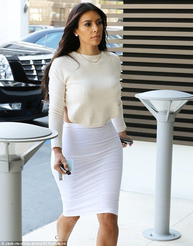 Kim Kardashian flashes her bra in revealing ensemble as she