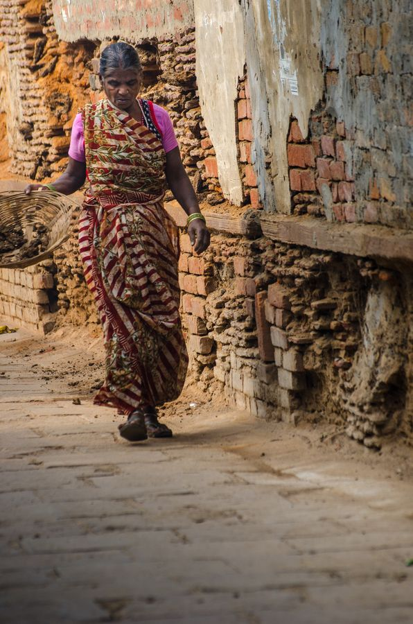 Woman in Varanasi, India dries cow feces for fuel