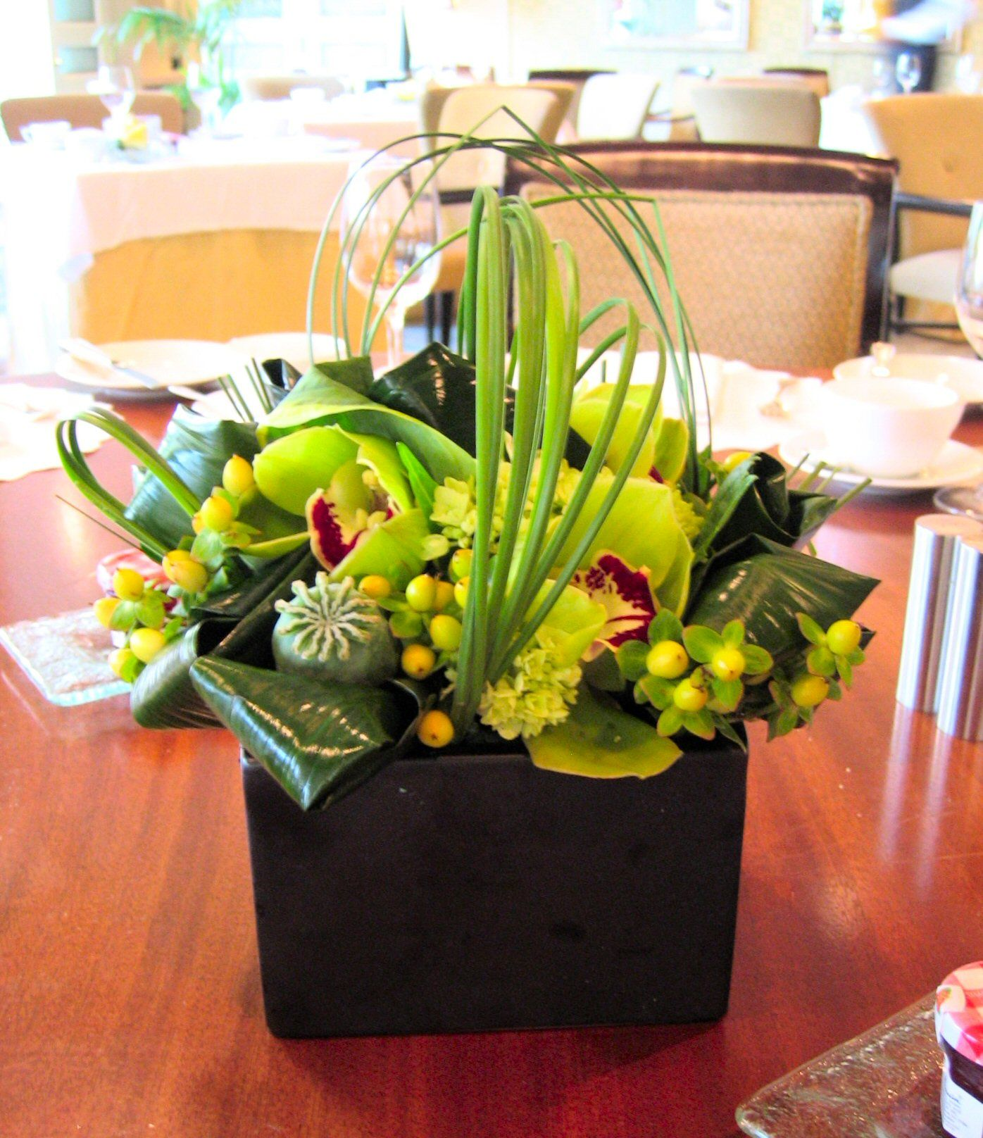 Modern Flower Arrangement With Green Cymbidium Orchids, Hypericum Berries, Poppy