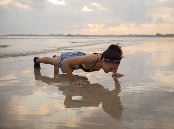 Push up on beach by lzf. Fitness asian woman doing pushups at sunset seaside, healthy lifestyle conc...
