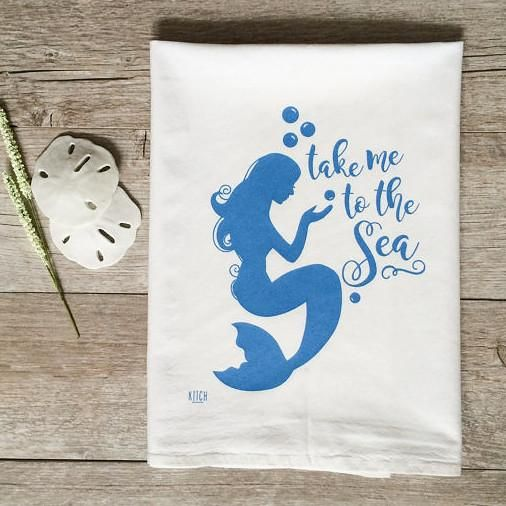 """Who's ready for the beach?!? This is a super fun Mermaid, the towel reads, """"Take me to the sea"""", PERFECT for your summer or retro kitchen! This is a natural cotton flour sack dish towel measures approximately 28""""x29"""", turquoise print measures approximately 9"""" high 100% MACHINE WASHABLE cotton."""