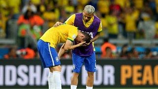 Oscar (L) is consoled by his teammate Dani Alves of Brazil after 1-7 defeat