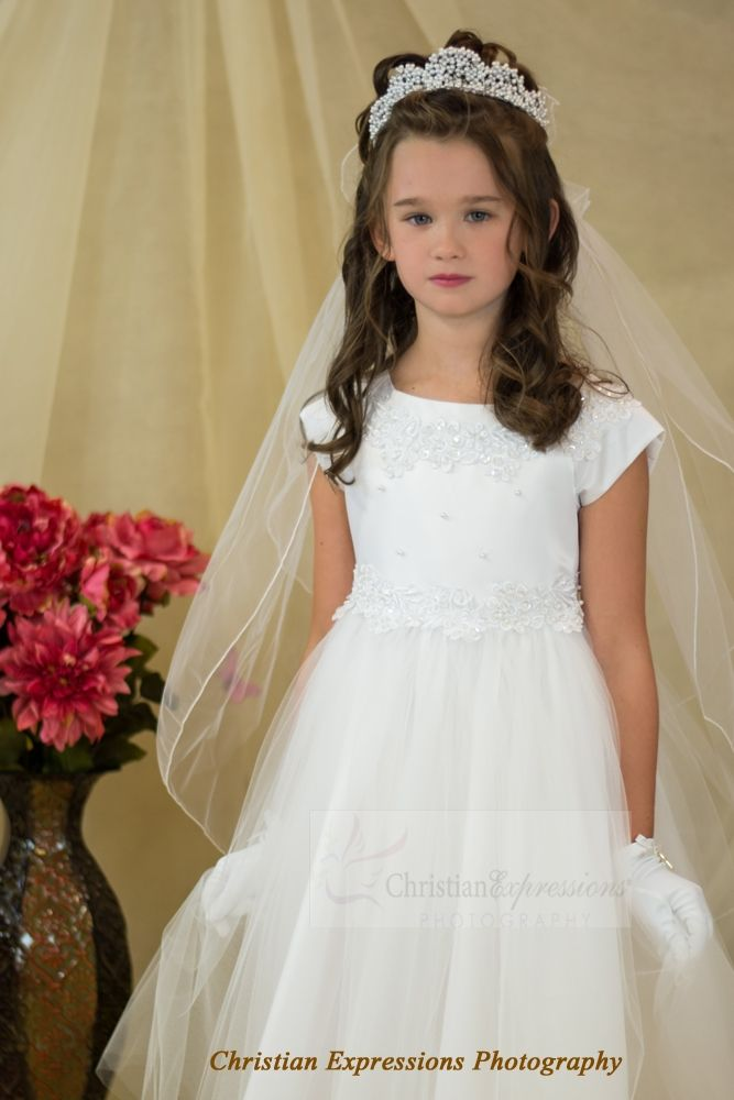 Pretty tea length first communion dress or flower girl dress. Made of polyester/acetate. This dress is made in the USA and is satin with organza overlay. Pearl accents throughout. Satin tie back