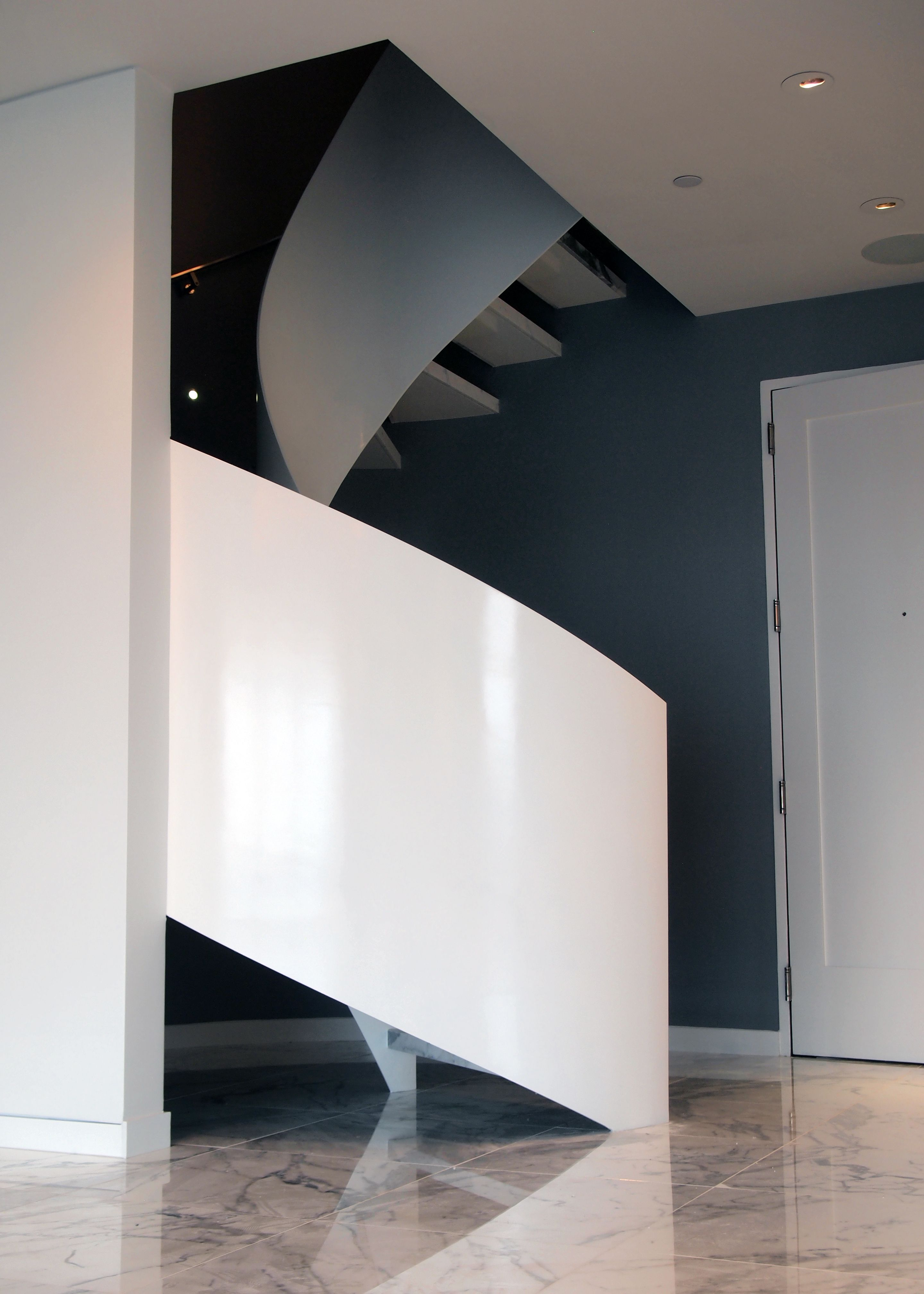 Curved Steel Plate Stair With Painted Finish And Stone Treads.