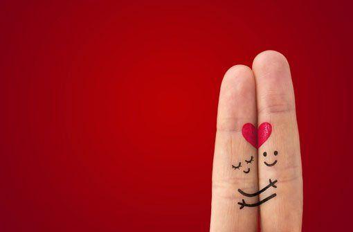 Zwei Finger, die ein Liebespaar bilden