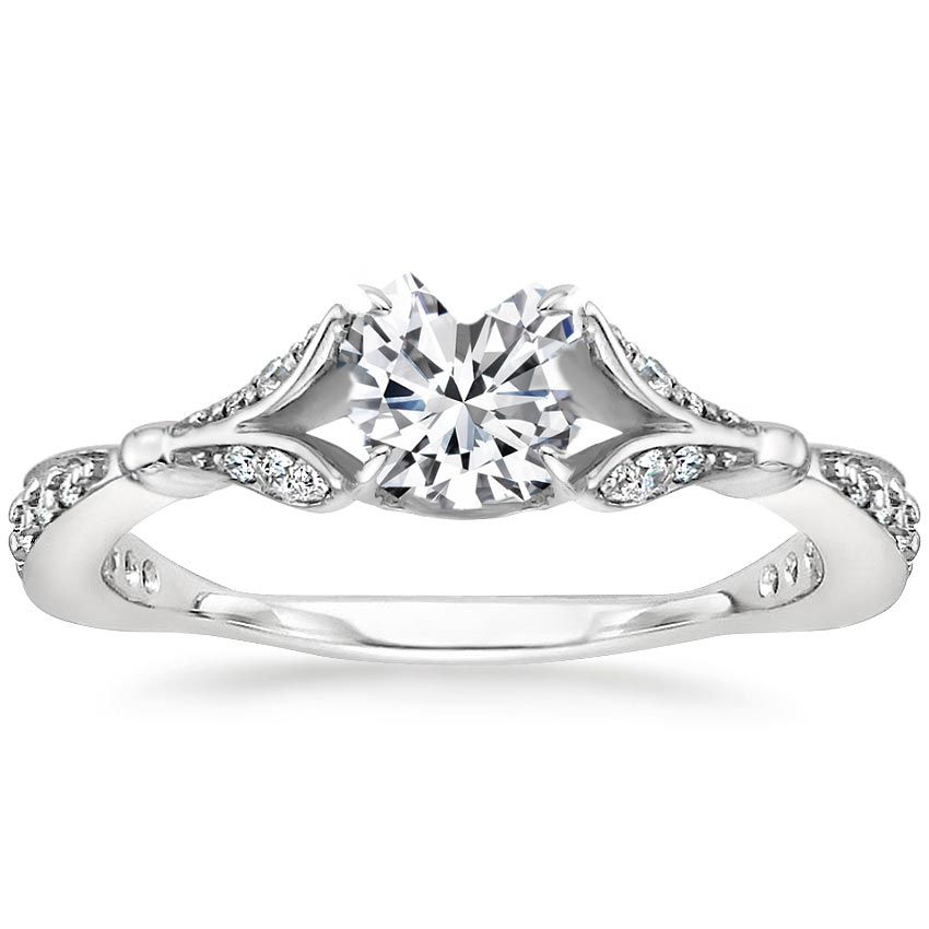 This feminine, nature-inspired ring showcases a dazzling center gem blooming from within a gallery of shimmering diamond petals. Additional diamonds sparkle along the band, which delicately tapers for a beautiful and unique look.
