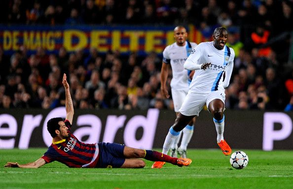 Yaya Toure of Manchester City goes past the challenge from Pedro of Barcelona during the UEFA Champions League Round of 16, second leg match between FC Barcelona and Manchester City at Camp Nou on March 12, 2014 in Barcelona, Catalonia.