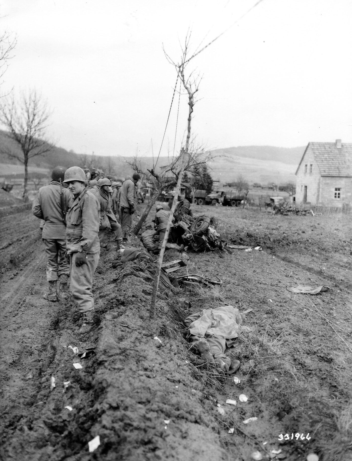Soldiers of the US 4th Infantry Division providing first aid to the driver of a Jeep that hit a mine near Hillesheim, Germany. In the foreground lies the jeep's passenger, who died instantly, March 1945.
