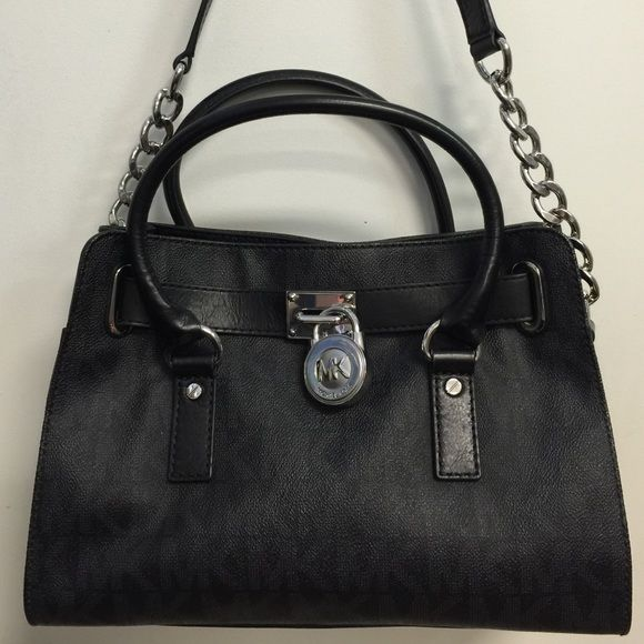 """Michael Kors Handbag Black This is a gorgeous bag and is in excellent like-new condition. Dual handles along with an attached shoulder strap measuring 11.5"""" long. Inside has one side zippered compartment and two utility pockets. Bag measures approx 13"""" long x 9"""" high x 5"""" deep. Has 4 metal feet on bottom. Michael Kors Bags"""