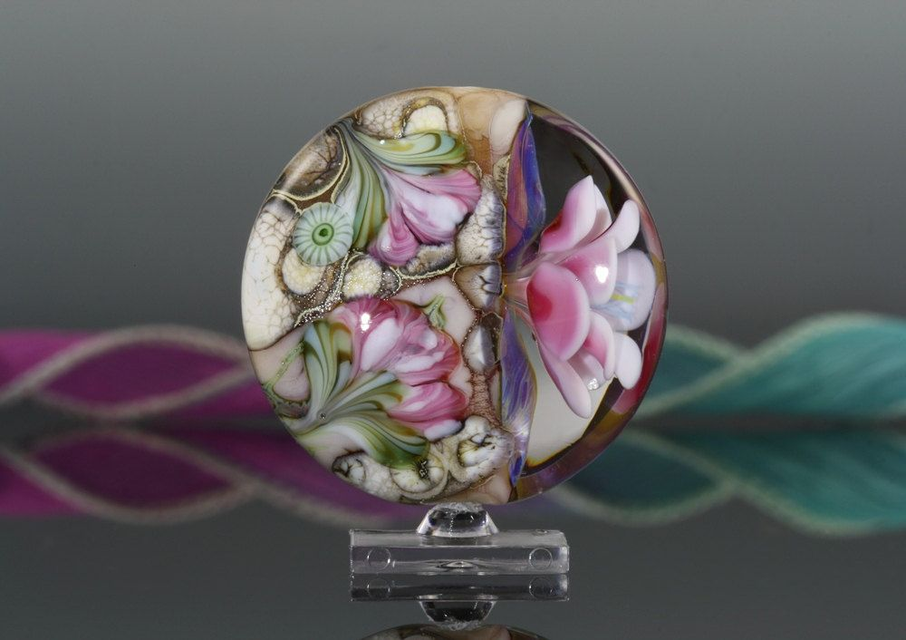 This is a lampwork glass focal bead. The glass bead has a floral pattern on one side, which is contrasted with an encased 3-D flower on the other side. The bead design has some of my own murrini.