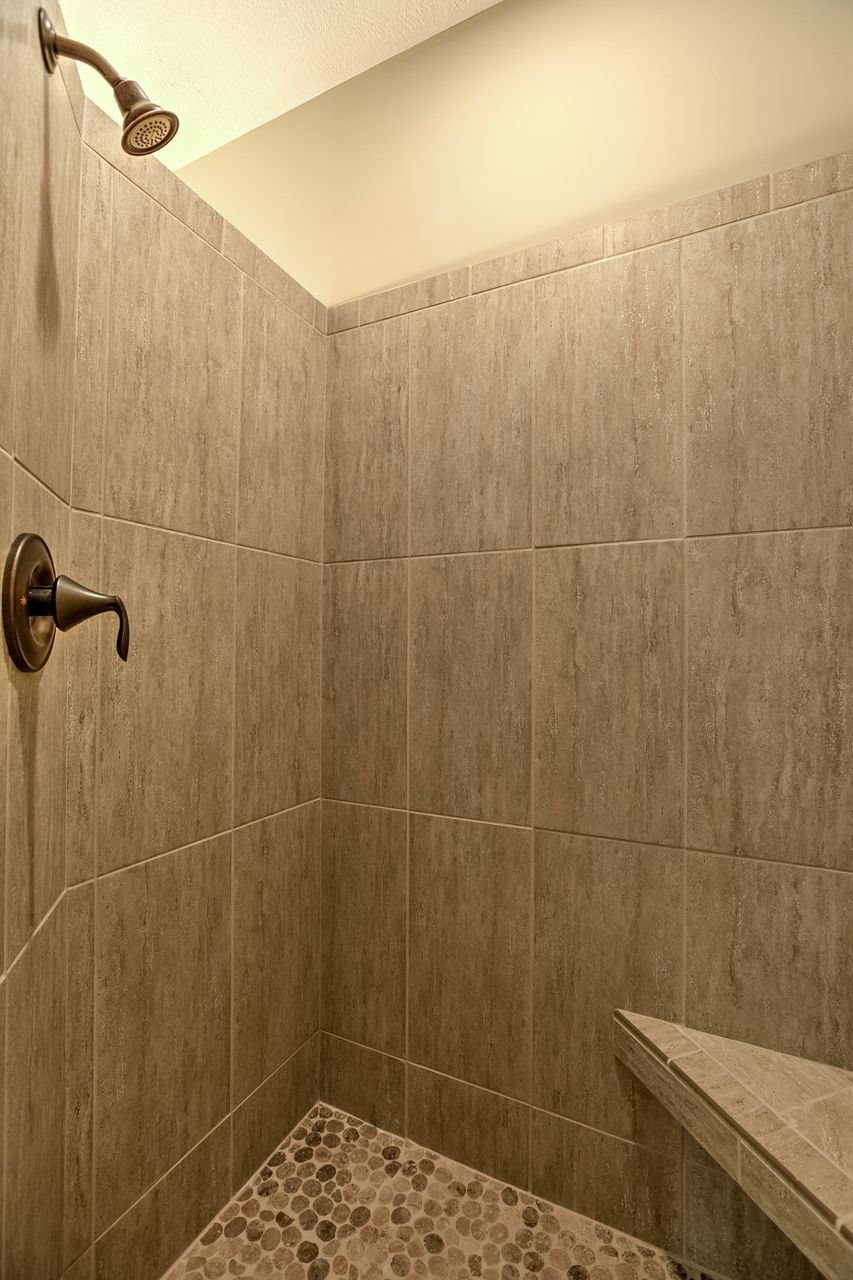 Tile master shower with pebble floor; corner shower seat | Riviera ...