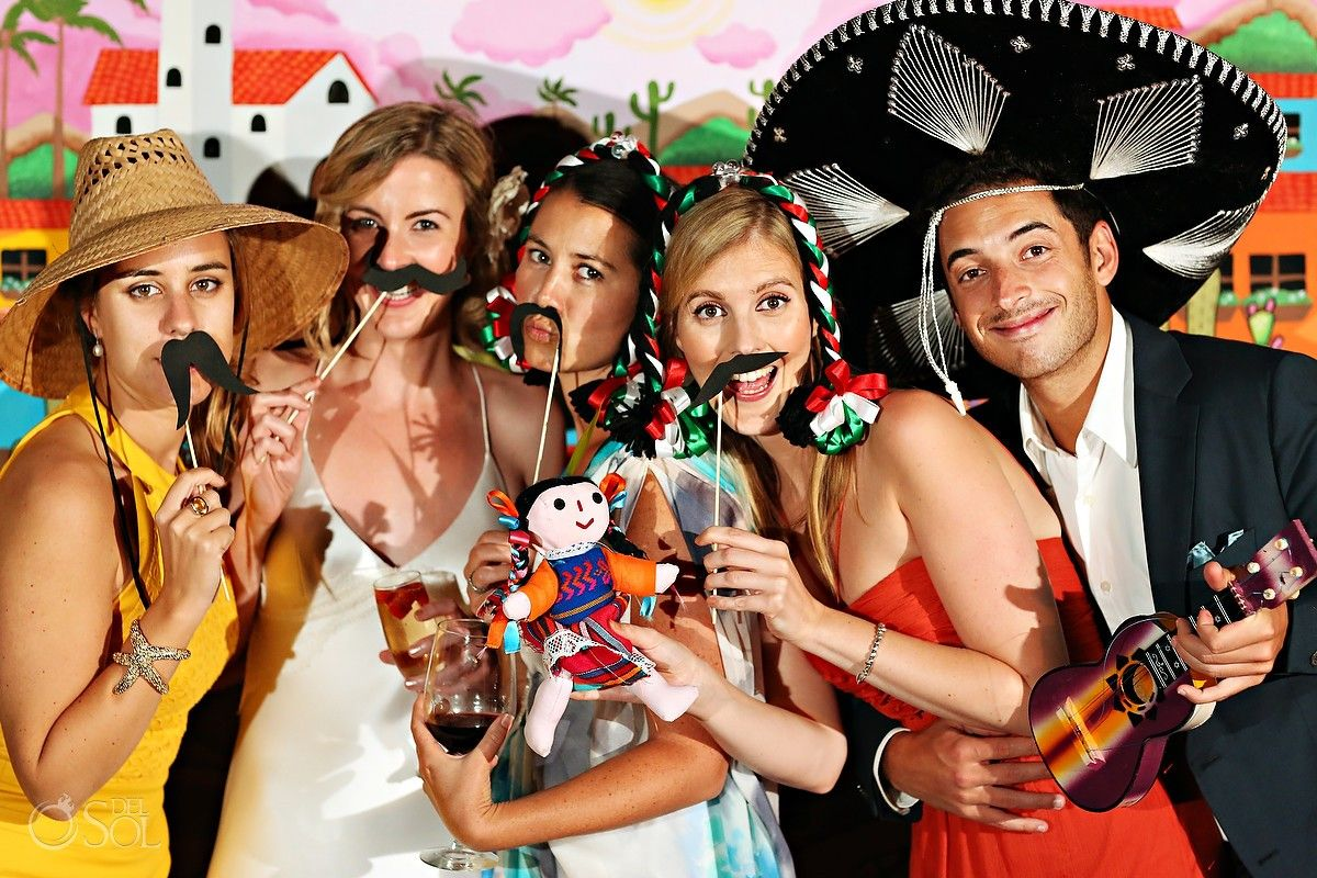 Destination wedding in Jalisco, Mexico! Photobooth fun at Georgia and James wedding in Yelap,a Mexico.  A friend of James gifted a stunning painting to the couple as a wedding present. They decided to use it as a background for this group of candid snaps with props, a perfect combo to go along with their …