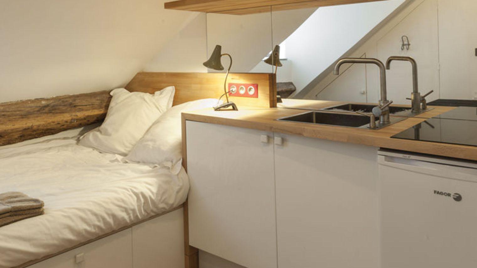 Un grand lit et une cuisine toute équipée dans un studio de 10m2 à ...