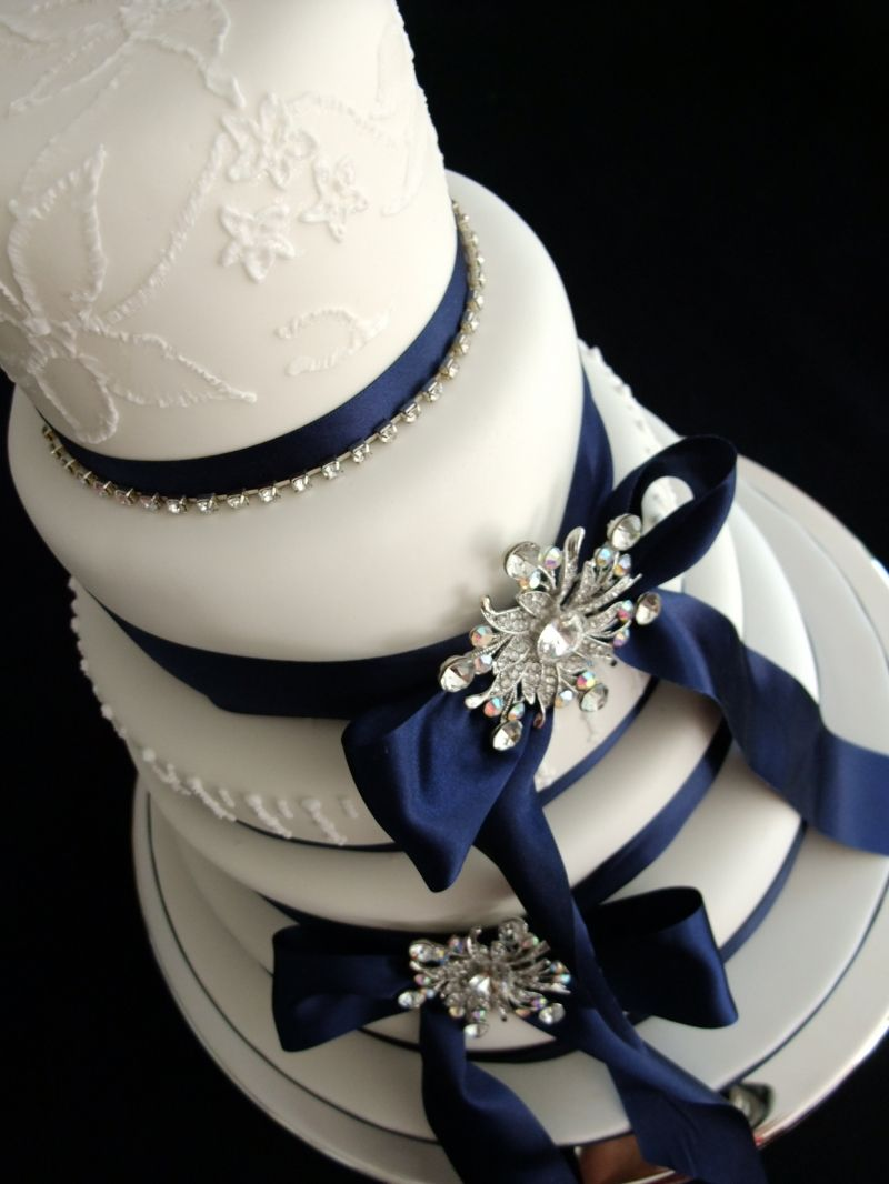Elegant wedding cake with navy ribbon and jewel accents